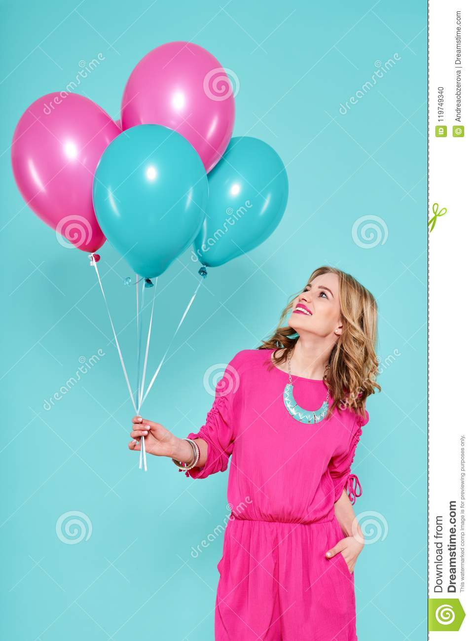 Gorgeous young woman in party summer dress holding bunch of colourful balloons, isolated over pastel blue colored background.