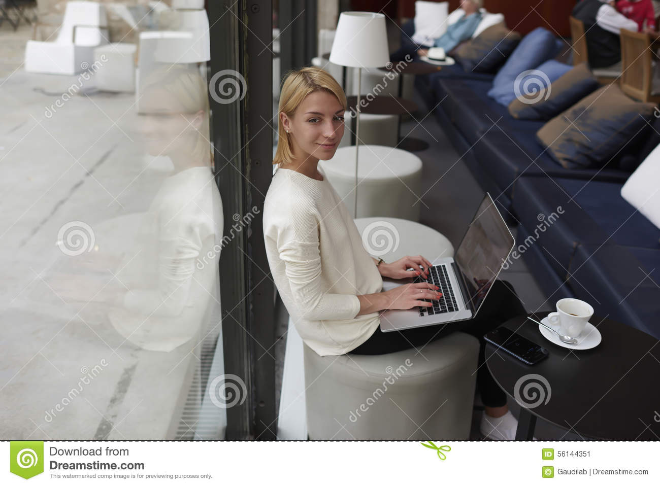 Gorgeous young woman sitting with open laptop computer in modern coffee shop or hotel interior