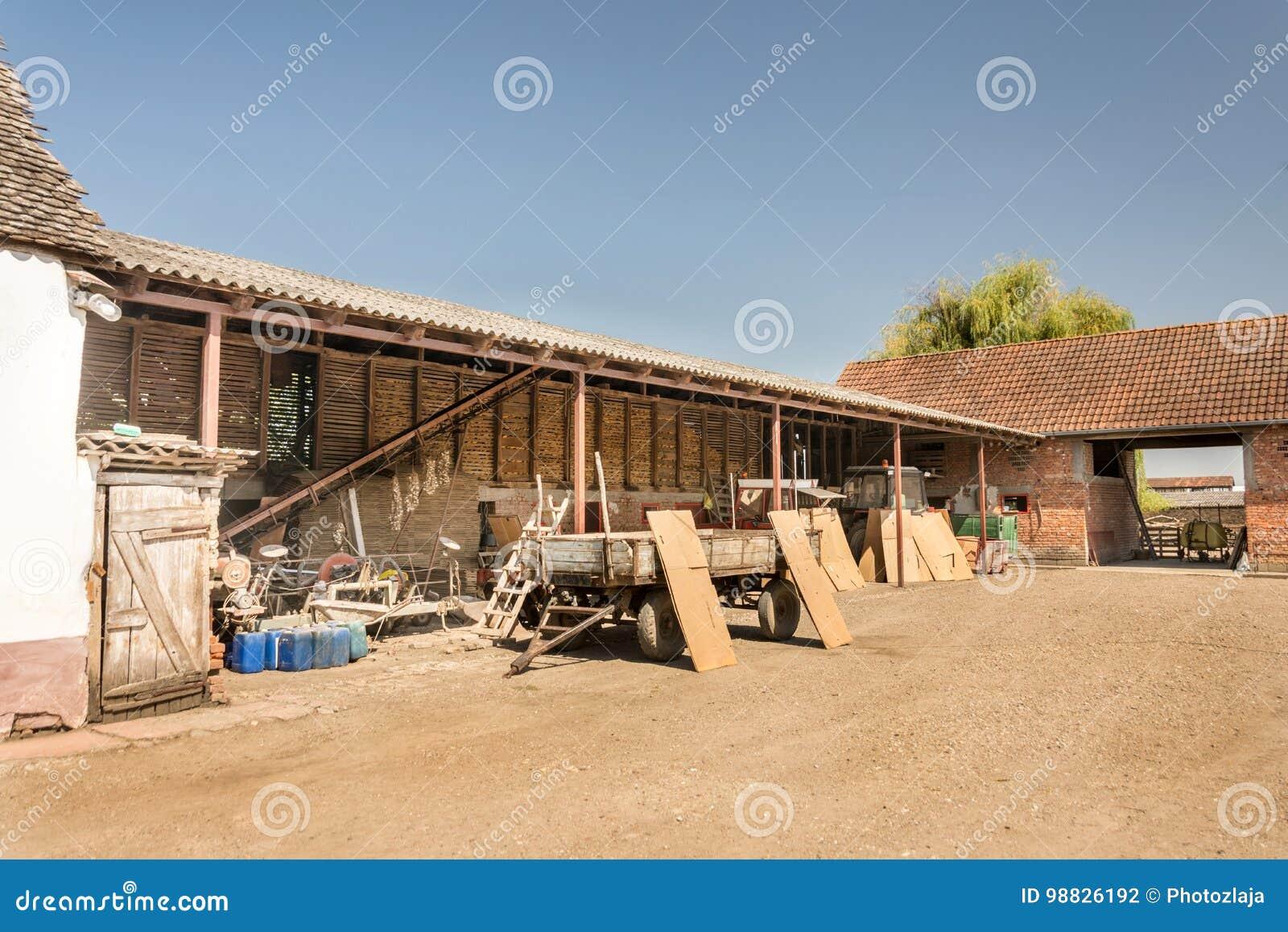 Gospodarstwo domowe w wiosce z stajenkami i ciągnikami w jardzie
