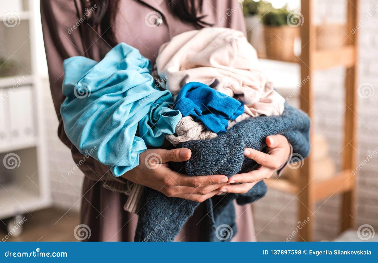 Gospodyni domowa starannie trzyma stos odziewa