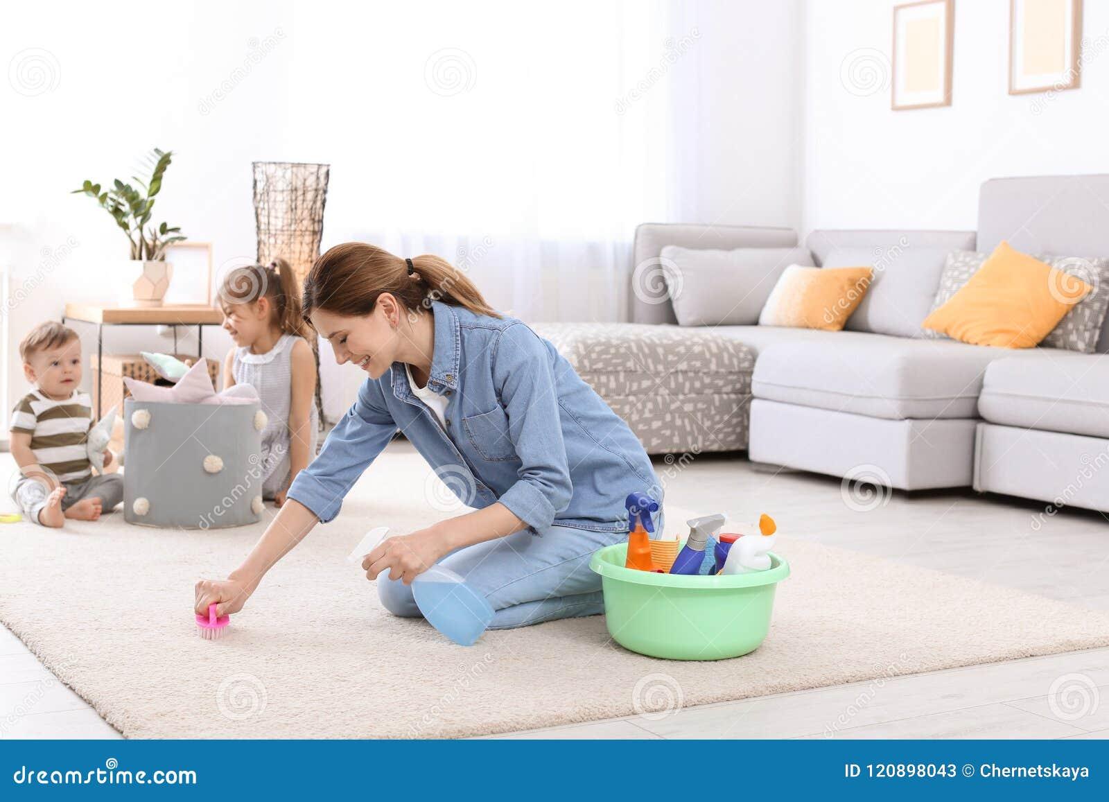 Gospodyni domowej cleaning dywan podczas gdy jej dzieci