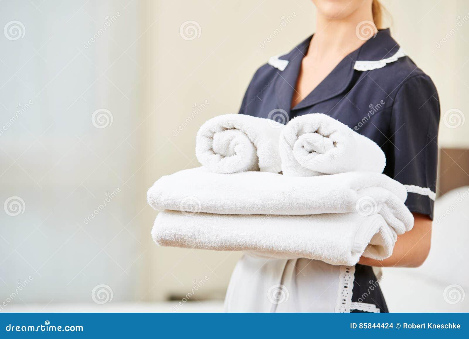 Gosposia z świeżymi ręcznikami podczas housekeeping