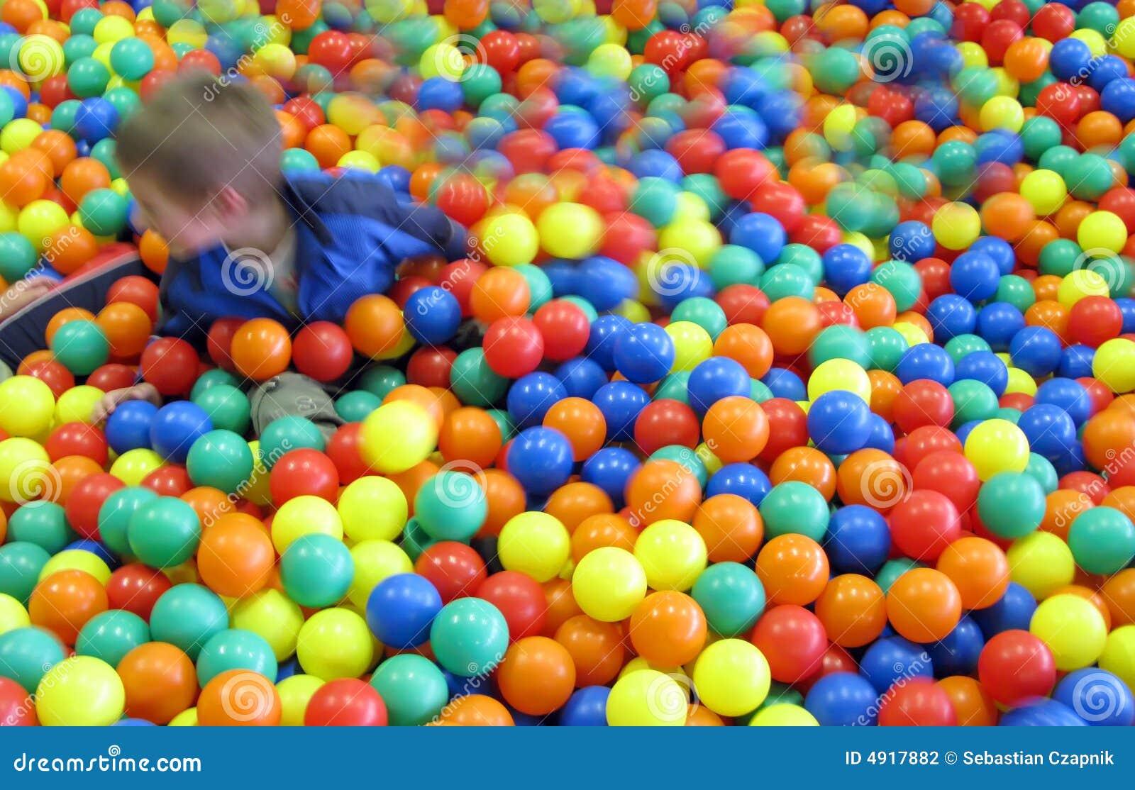 Gosse dans les billes colorées d amusement