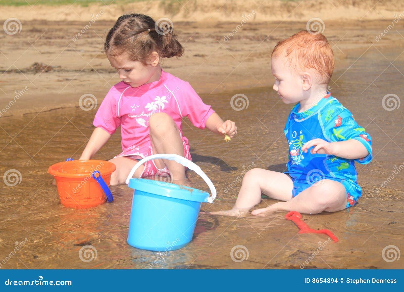 Gosses d enfants de plage jouant l eau de jouets