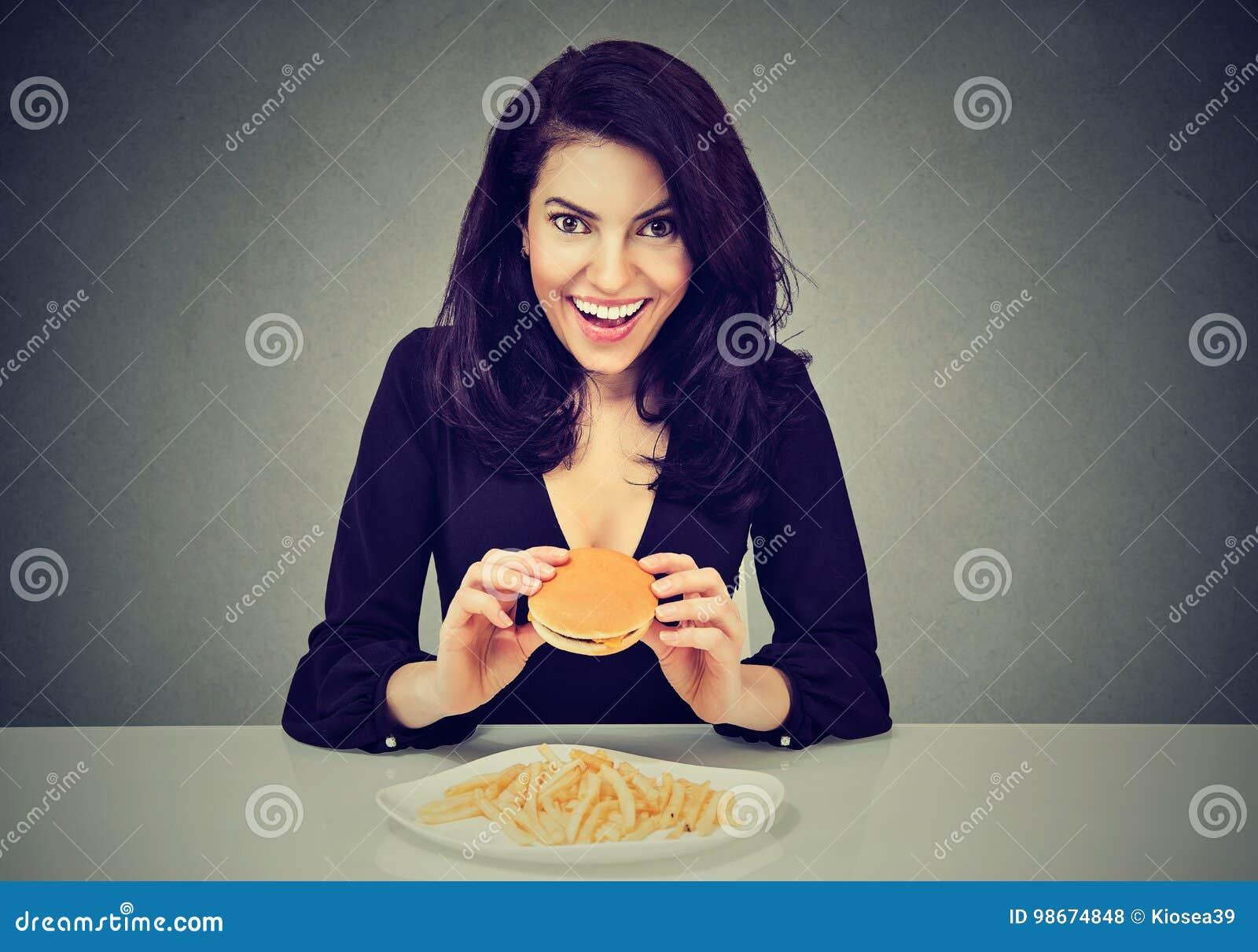 Gosta do fast food Jovem mulher feliz que come o cheeseburger e as batatas fritas