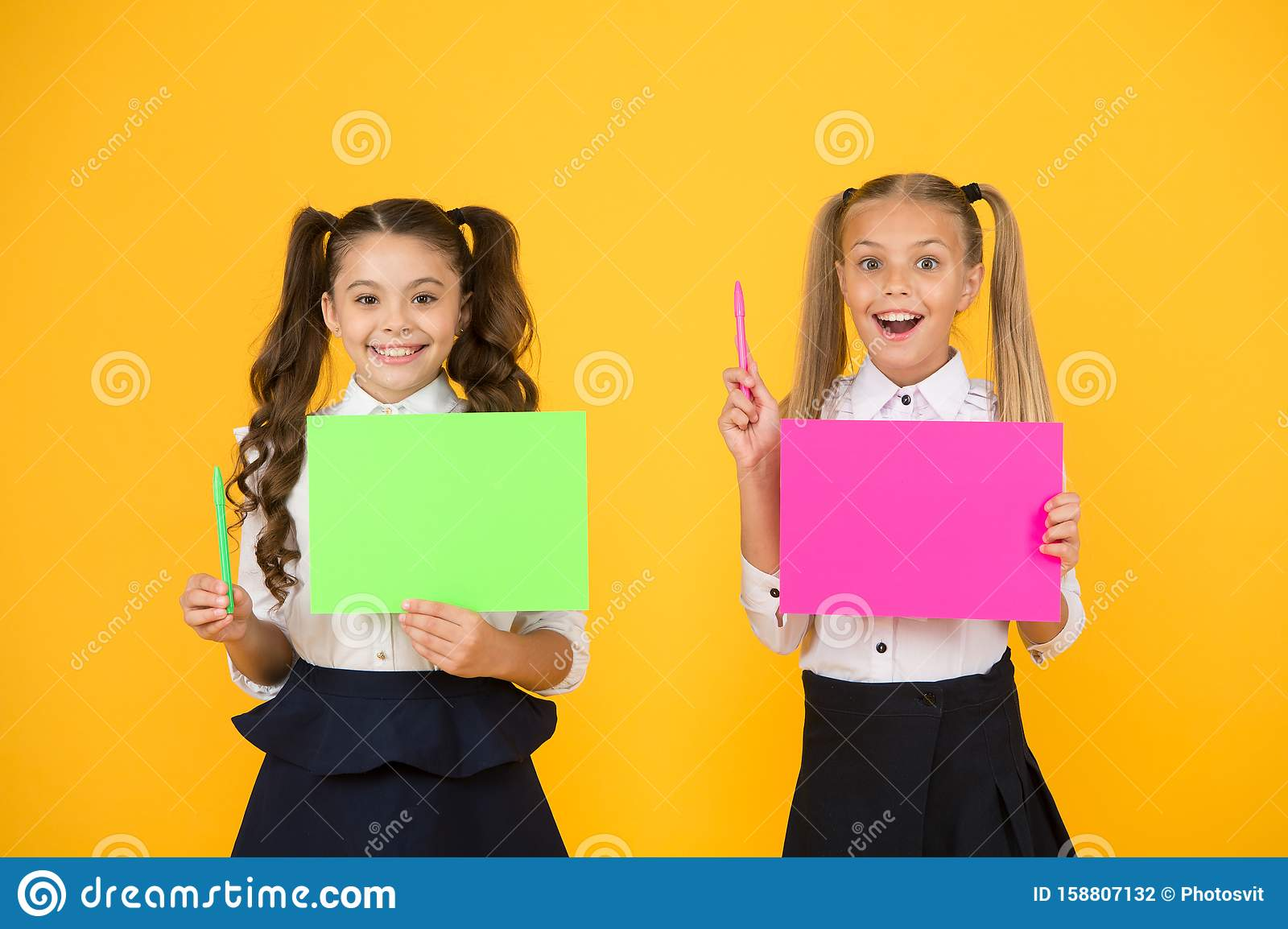 Got idea. Small cute kids smiling of genius idea. Happy girls holding paper sheets for writing idea on yellow background