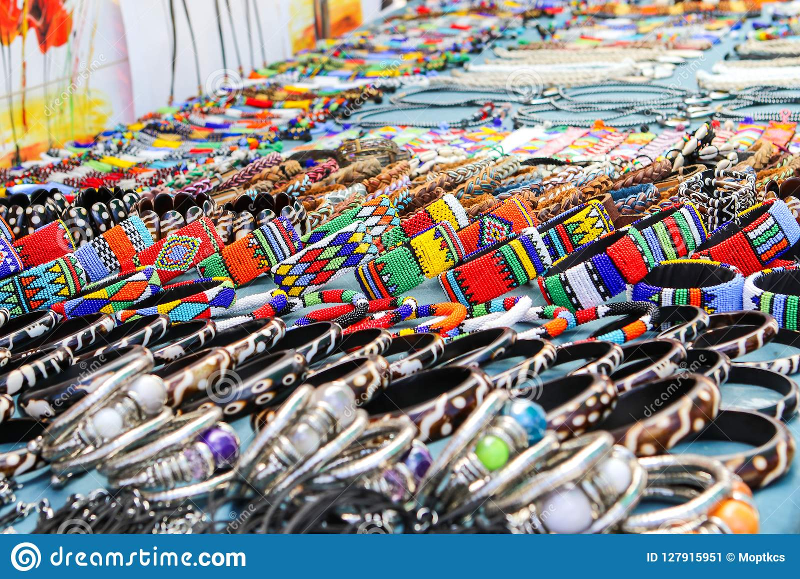 Gotas coloridas y pulseras, brazaletes y collares hechos a mano de cuero en el mercado local del arte en Suráfrica