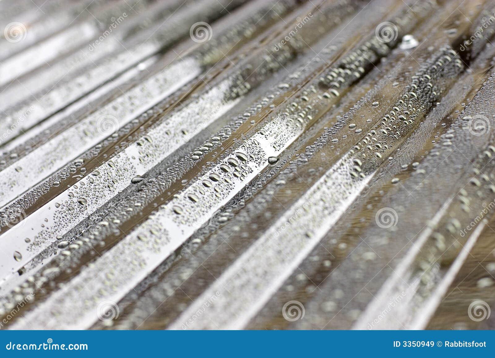 Gotas da água em telhado ondulado