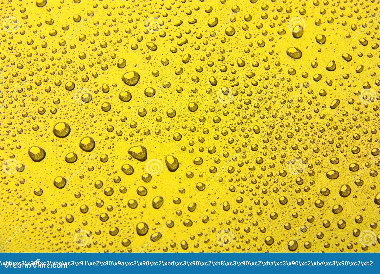 Gotas da água em um fundo da cor amarelo