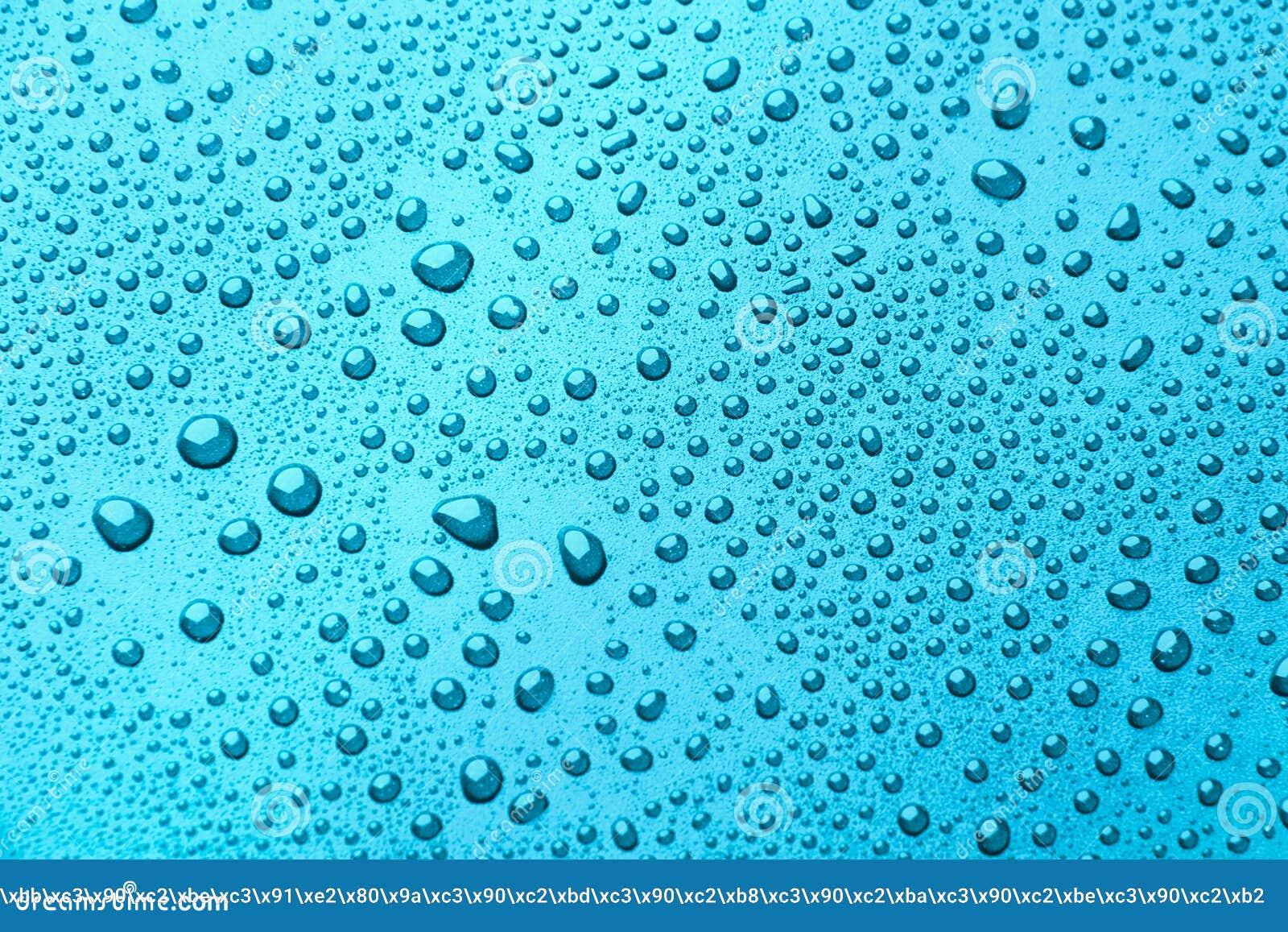 Gotas da água em um fundo da cor Luz - azul