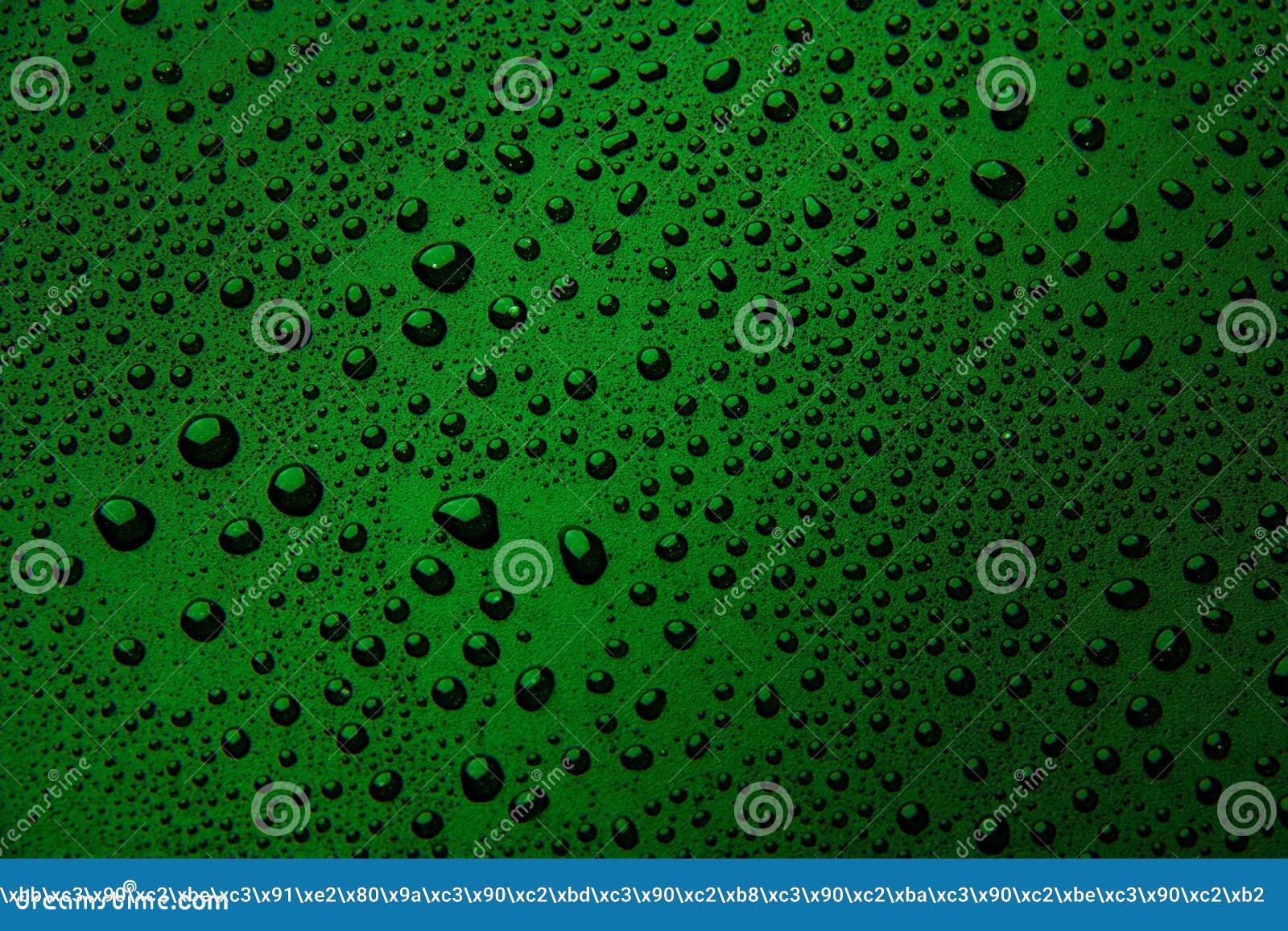 Gotas da água em um fundo da cor Verde