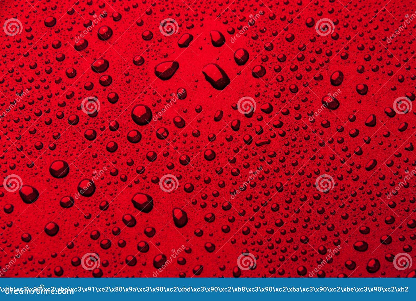 Gotas da água em um fundo da cor Vermelho