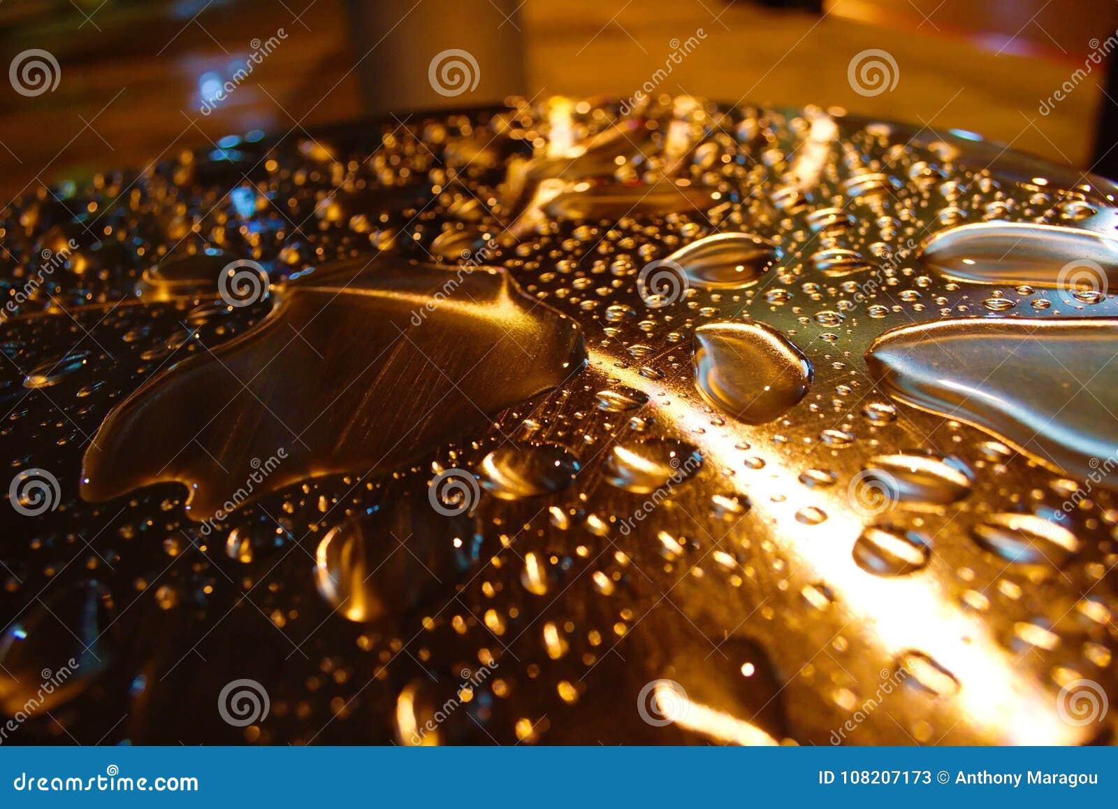 Gotas da água iluminadas na coluna do metal