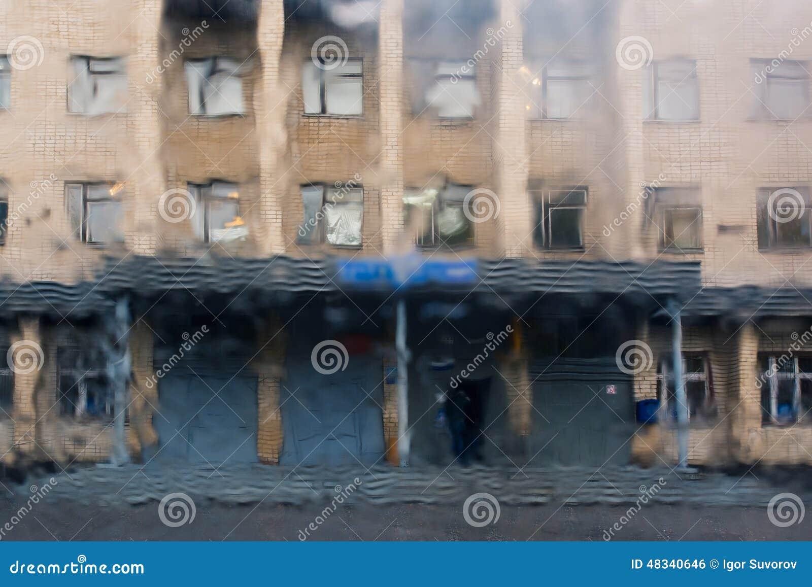Gotas da chuva em uma placa de janela, construções dentro