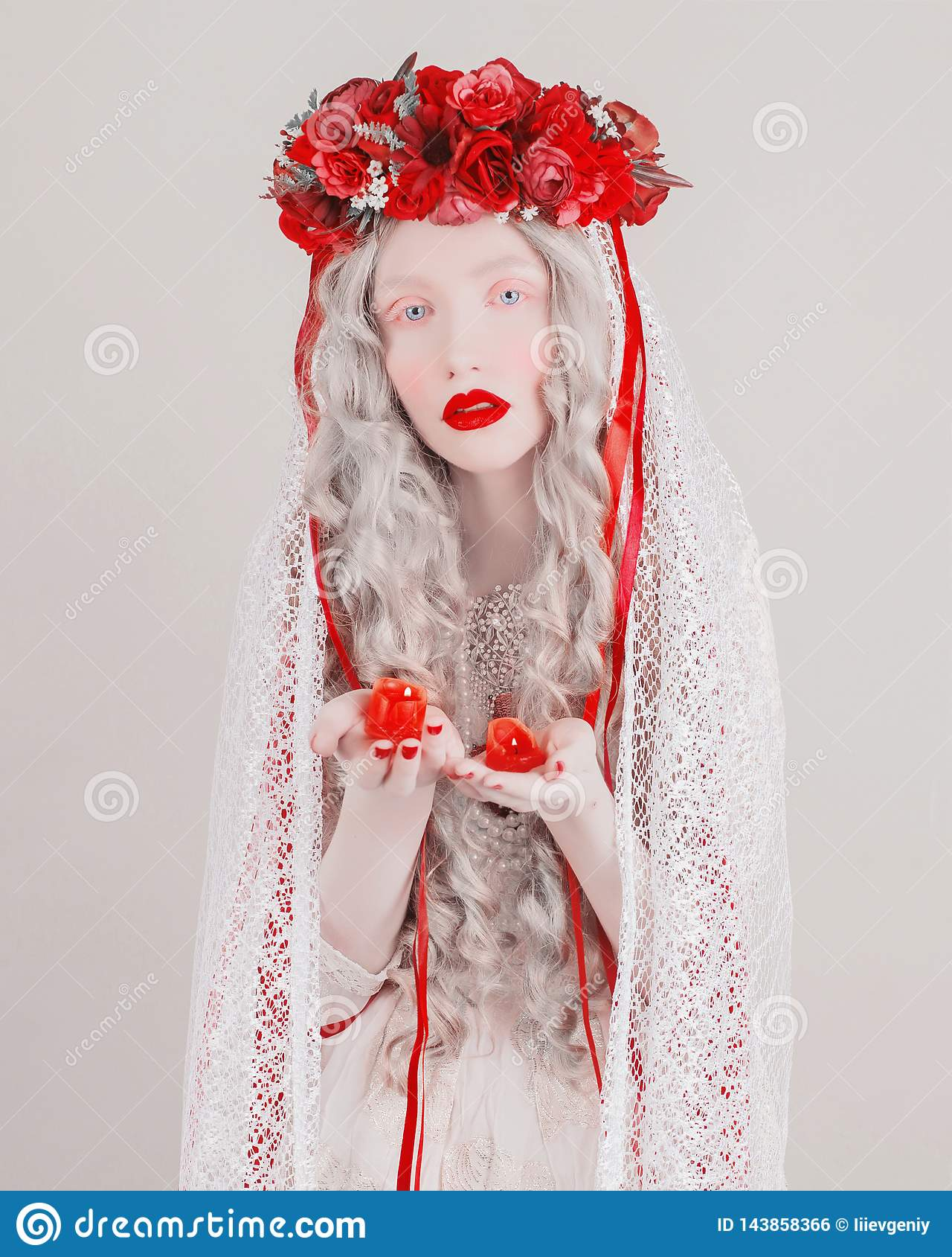 Gothic blonde woman vampire in flower wreath with pale skin and red lips. Mysterious creepy witch with long hair and candle.