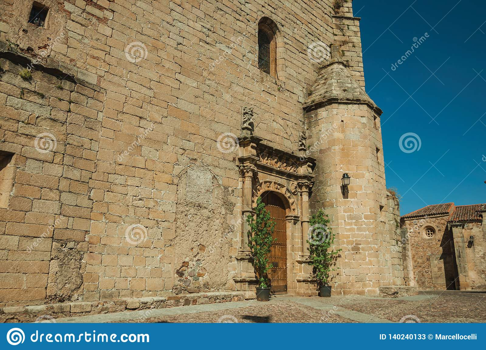 Gothic church facade with decorated wooden door at Caceres