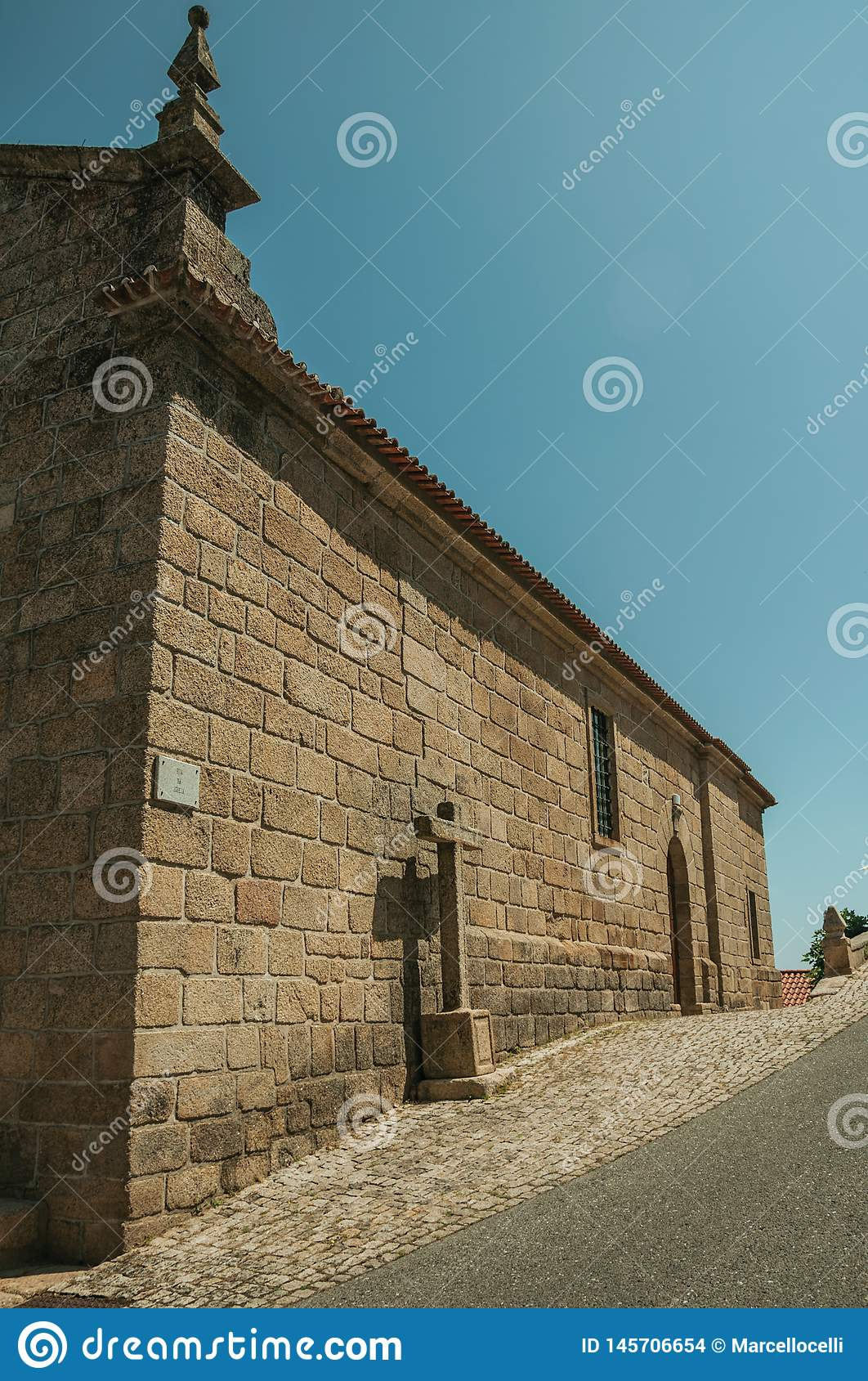 Gothic church with stone wall and cross at Monsanto