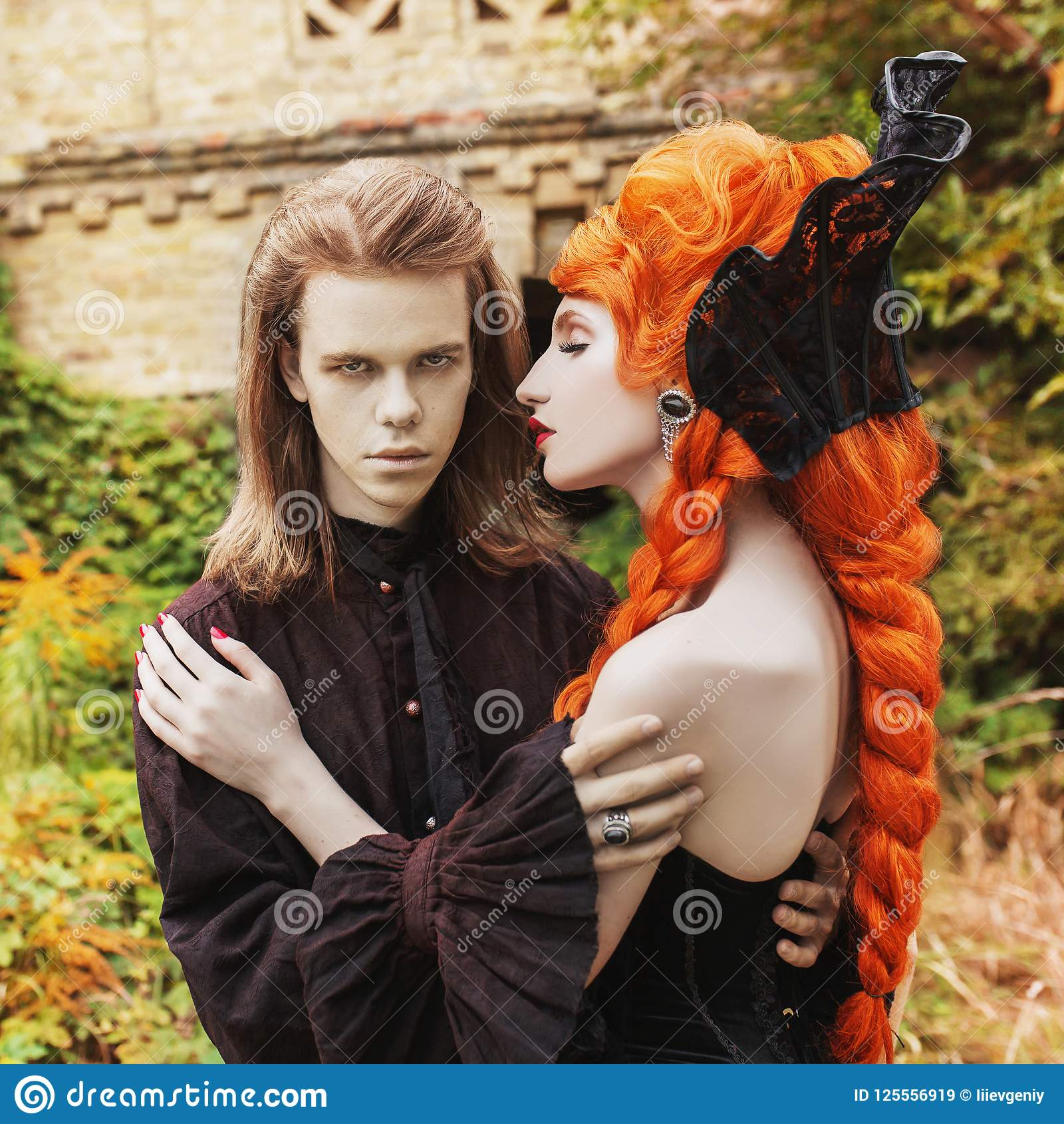 gothic couple in a halloween costume. pale undead vampire in dark