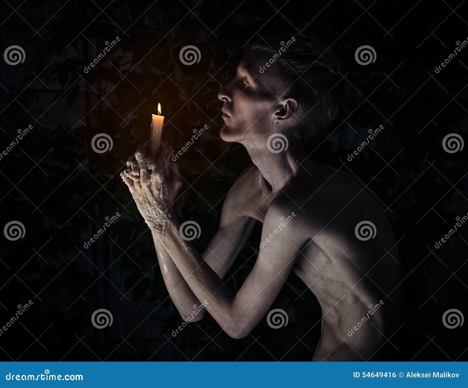 Gotisch en Halloween-thema: een mens met een kaars op zijn knieën met zijn ogen sloot en biddend, hete was op zijn handen