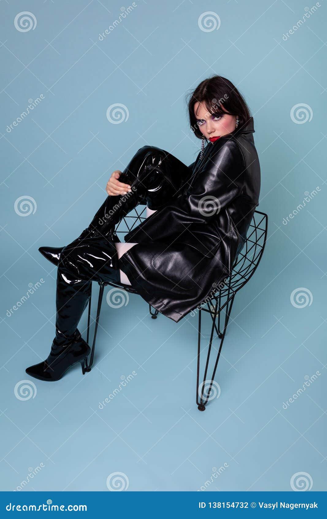 Gotisk flicka som bär den svarta klänningen och svarta kängor med svart kort hår