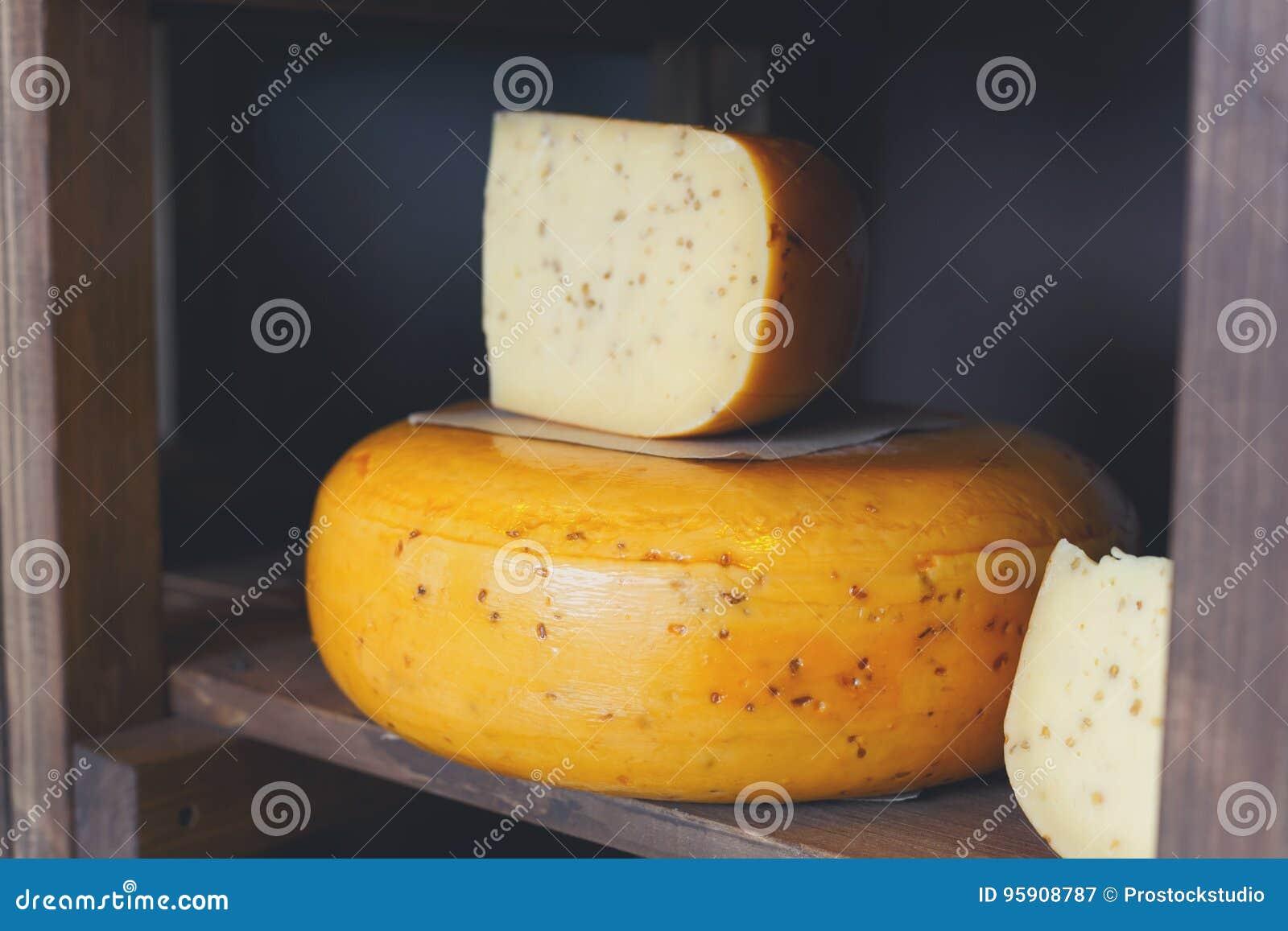Gouda ser jako koło i kawałek na drewnianej półce sklepu spożywczego sho