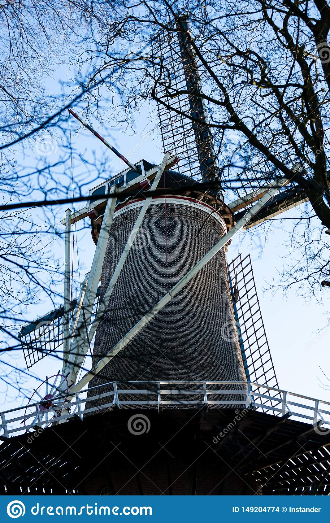 Gouda, South Holland/the Netherlands - January 20 2019: Picture of old windmill next to city park taken through tree branches