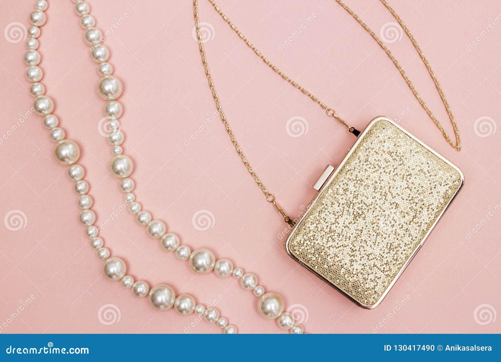 Gouden beurs en parelhalsband op roze achtergrond