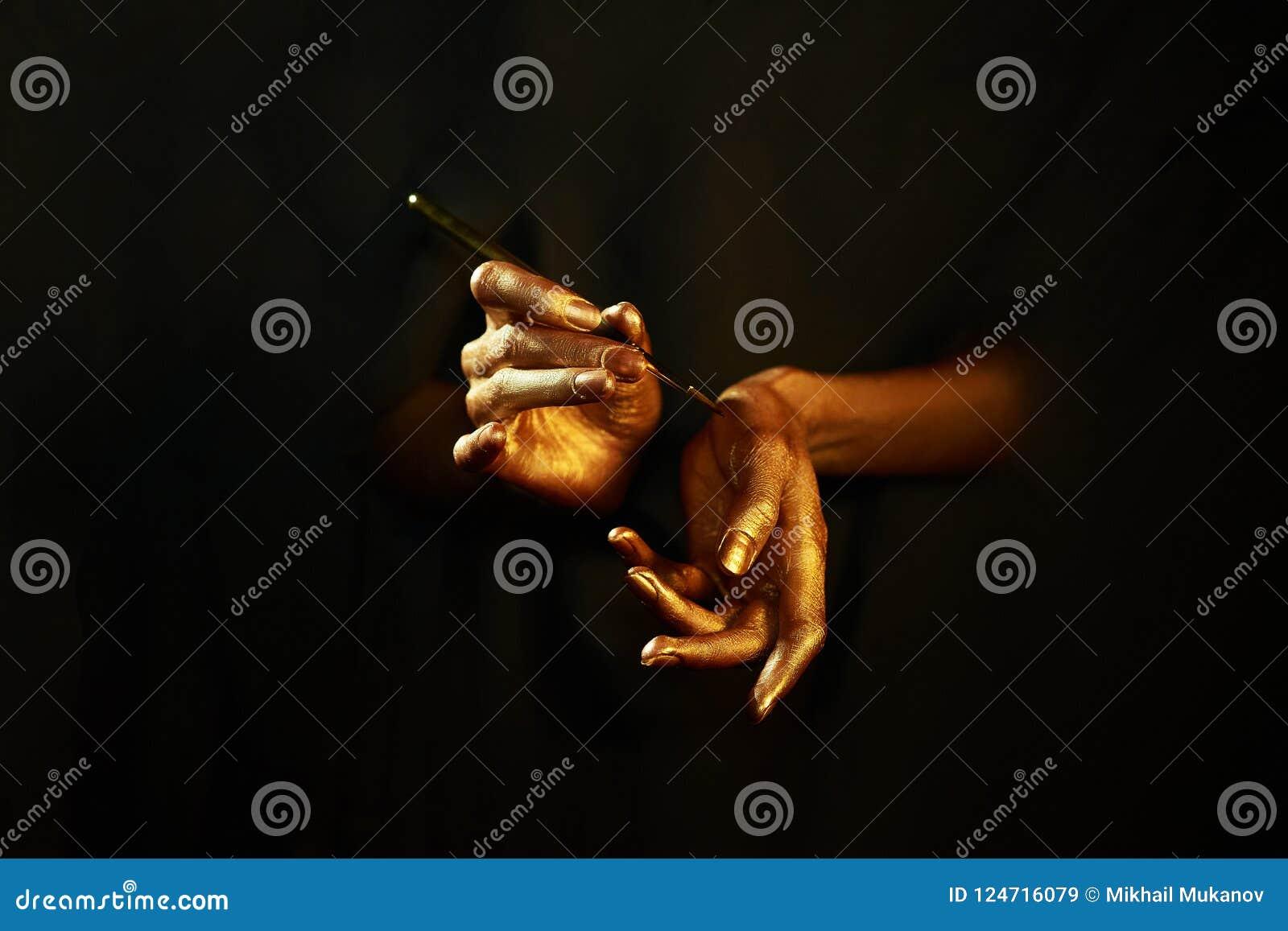 Gouden die handen witn borstel op zwarte achtergrond wordt geïsoleerd