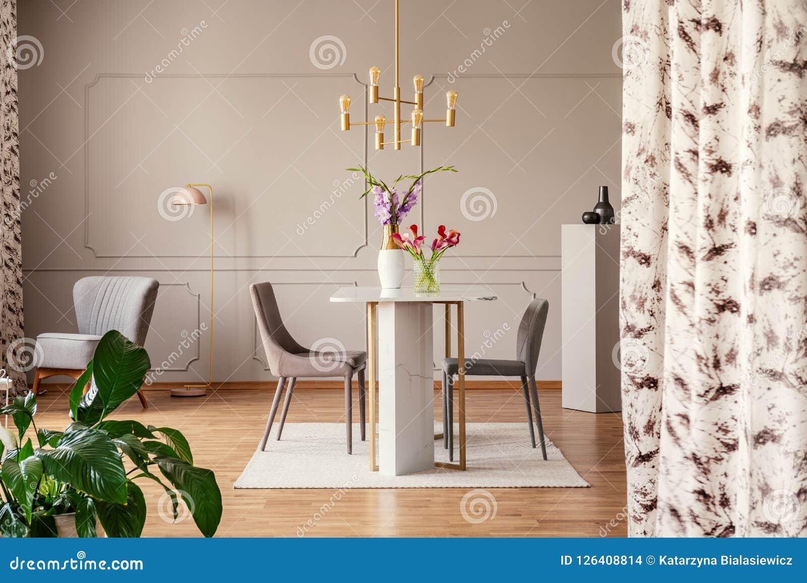 Gouden lamp boven stoelen en lijst met bloemen in elegant eetkamerbinnenland met installatie Echte foto