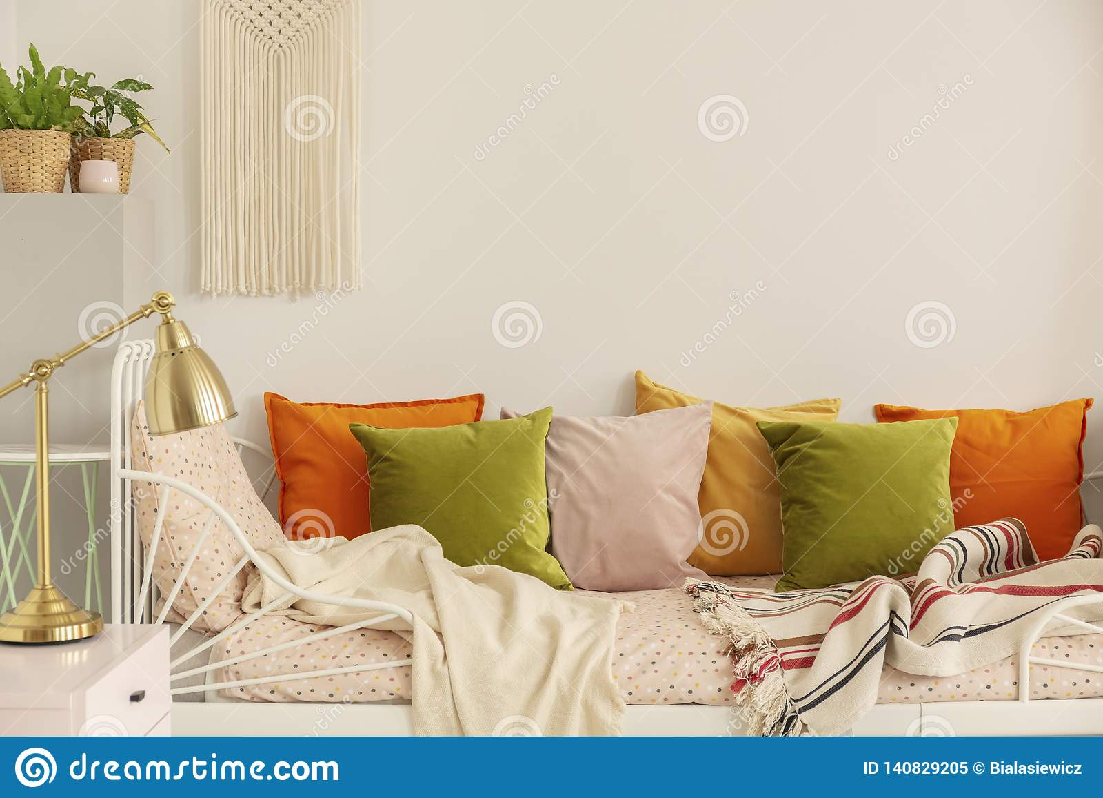 Gouden lamp op nightstand naast groene olijf, pastelkleur roze, gele en oranje hoofdkussens op enig metaalbed met gevormd