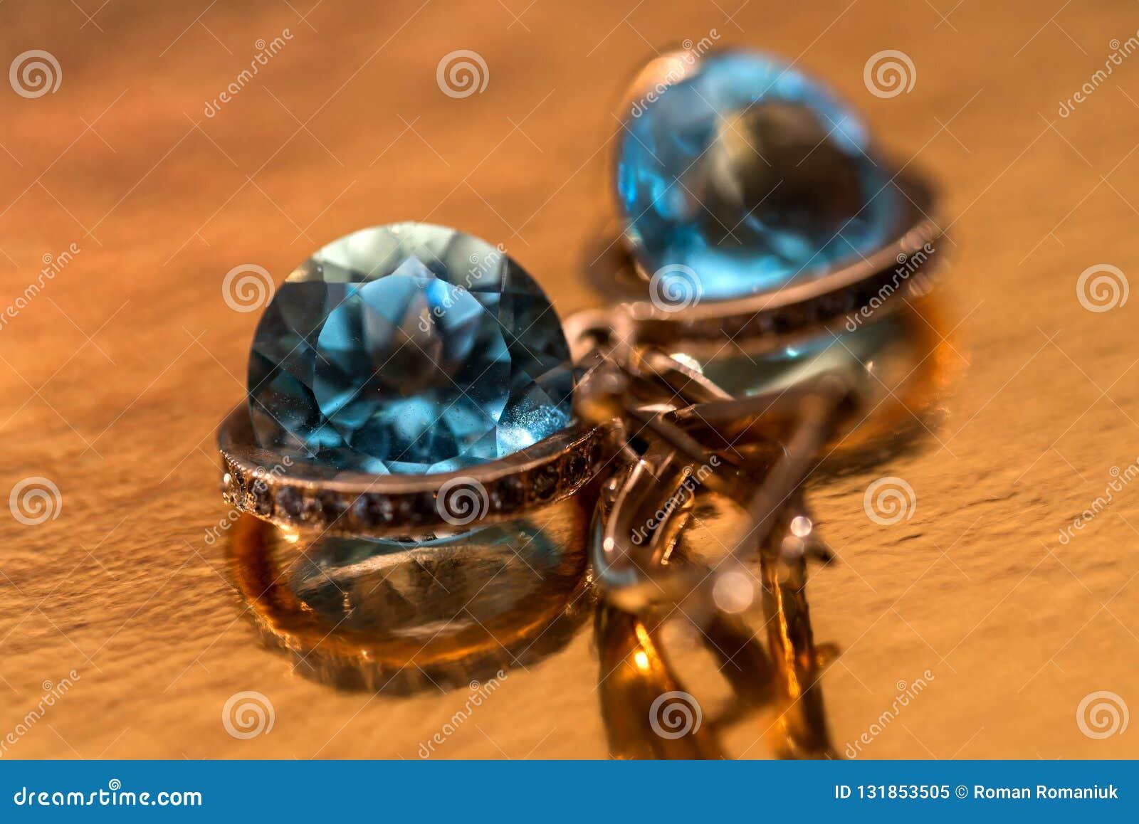 Gouden oorringen met kristallen op de achtergrond