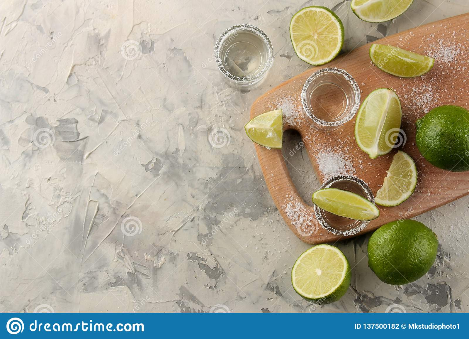 Gouden tequila in een glas schoot glas met zout en kalk op een lichte concrete achtergrond Staaf Alcoholische dranken Mening van