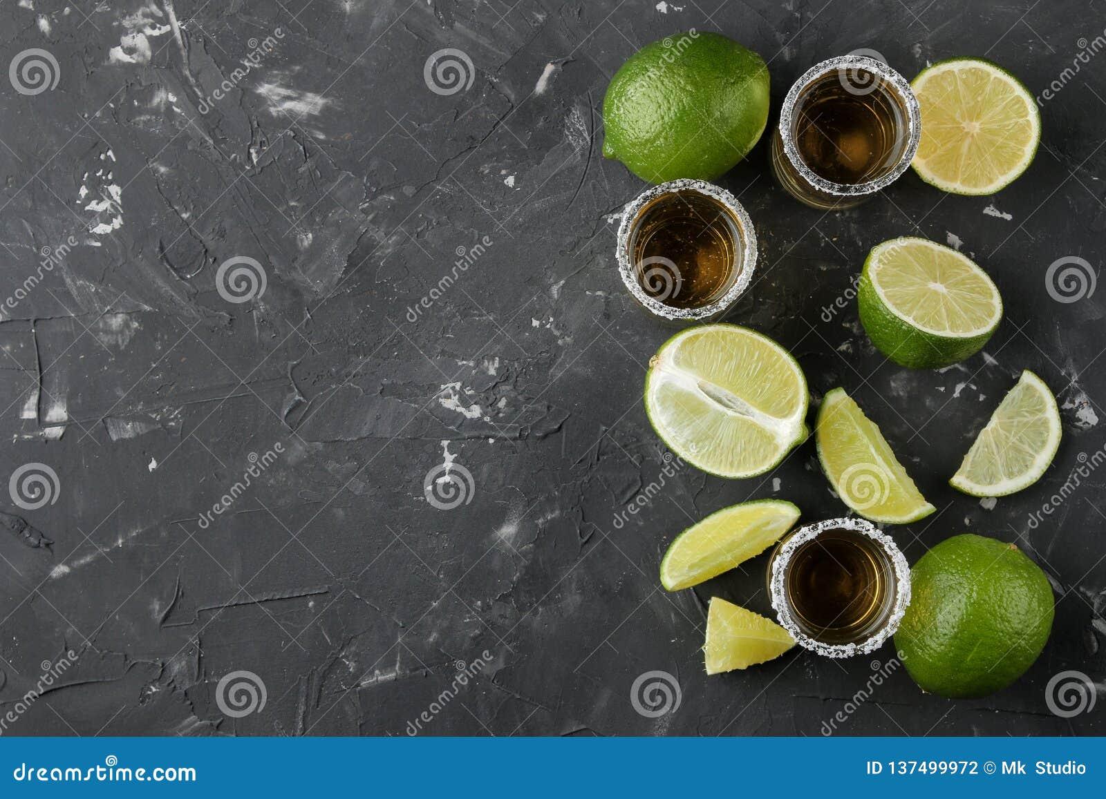 Gouden tequila in een glas schoot glas met zout en kalk op een zwarte concrete achtergrond Staaf Alcoholische dranken Hoogste men