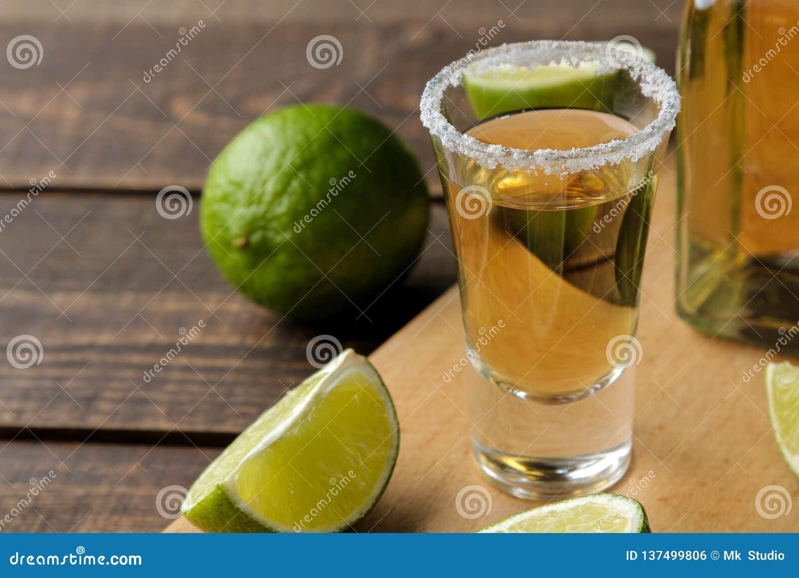 Gouden tequila in glas/glas- met zout en kalk dichte omhooggaand op bruine houten achtergrond