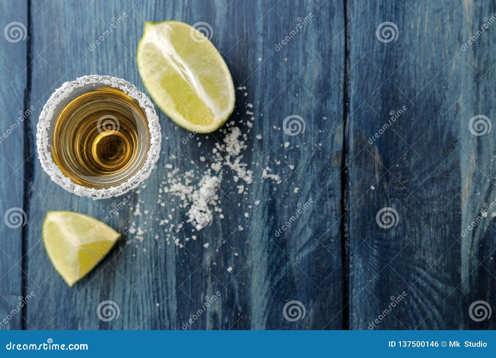 Gouden tequila in glas/glas- met zout en kalk op een blauwe houten achtergrond Staaf Alcoholische dranken Mening van hierboven Me