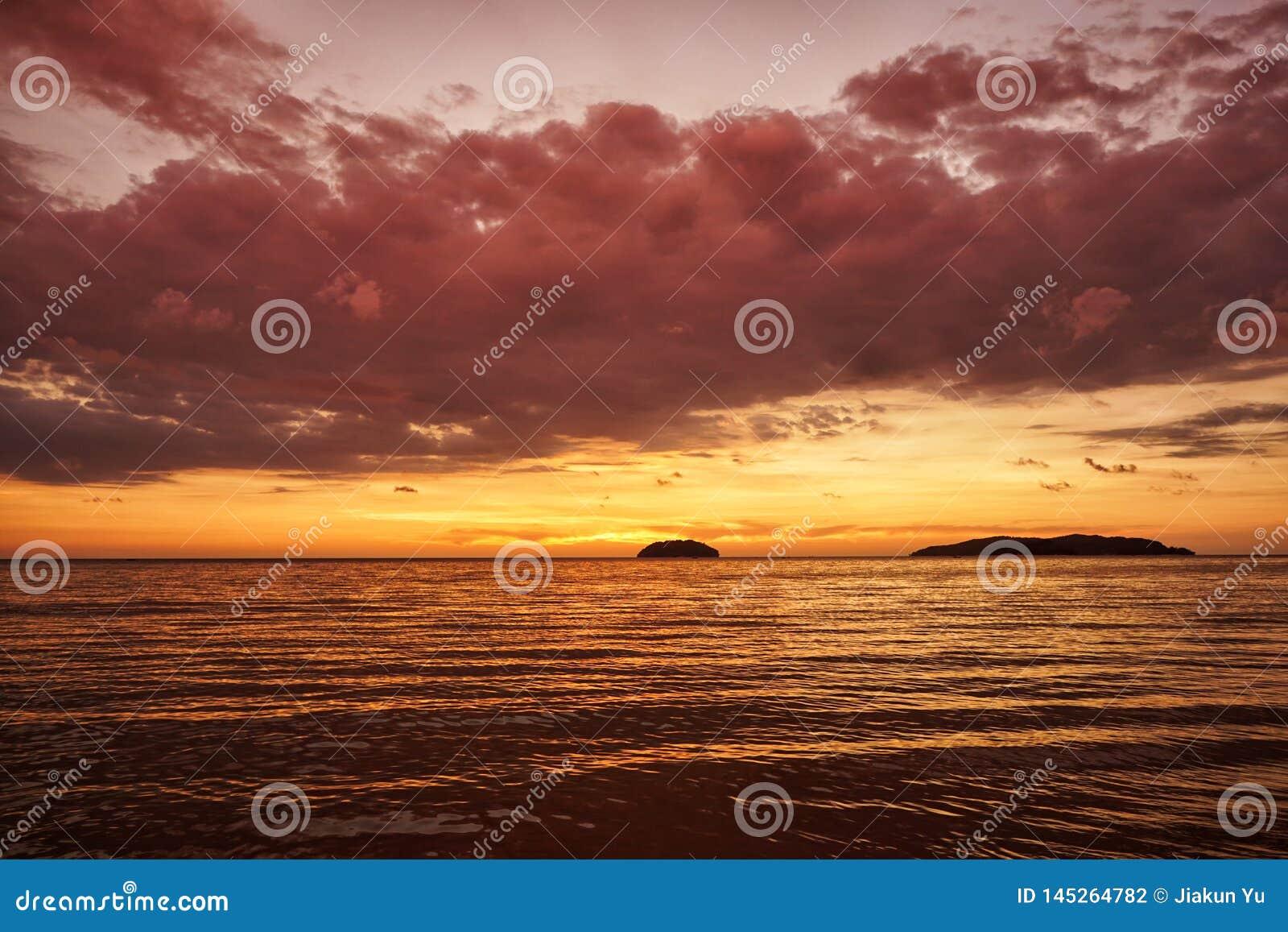 Gouden zonsondergang op het strand met donkere wolken en avondgloed Het overzeese bezinningsrode licht als zonsopgang