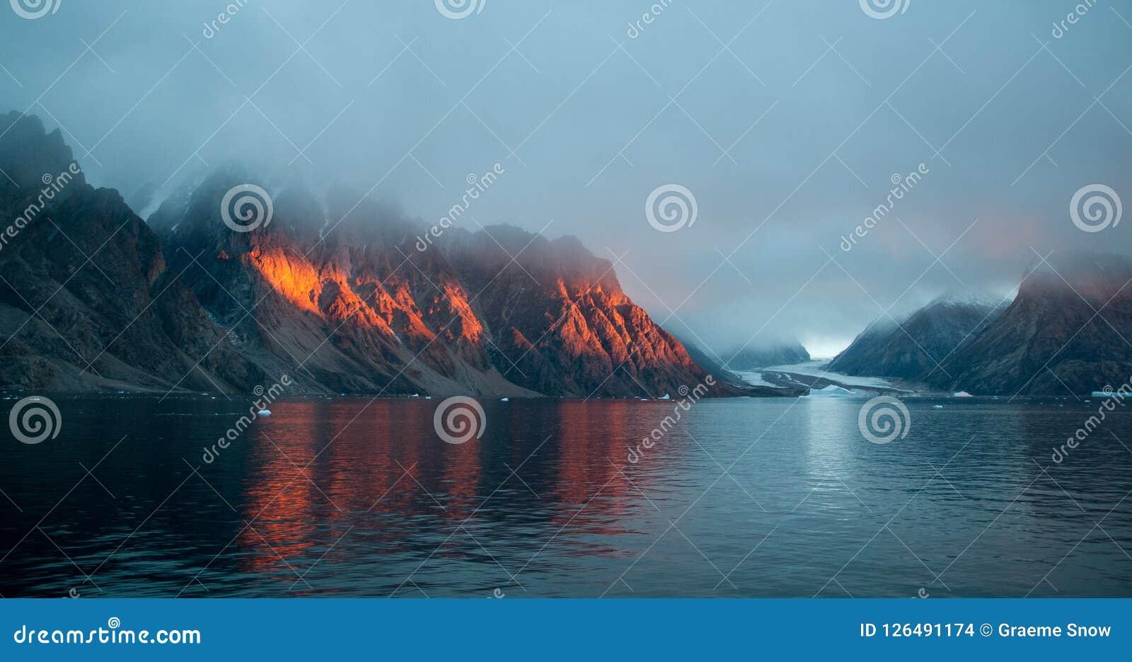 Gouden zonsonderganglicht op bergen, Scoresby Sund, Groenland