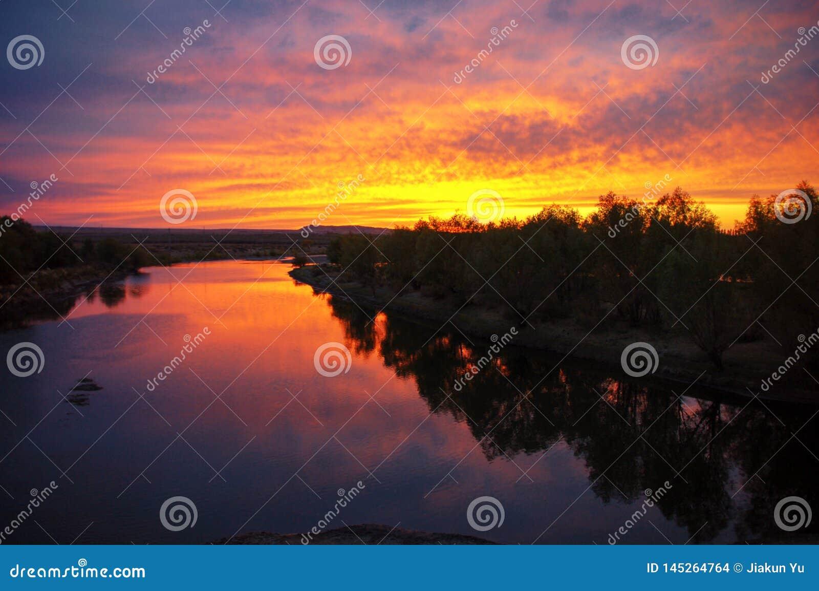 Gouden zonsopgang met kleurrijke vlammende wolken, het rode licht van de rivierbezinning als zonsondergang