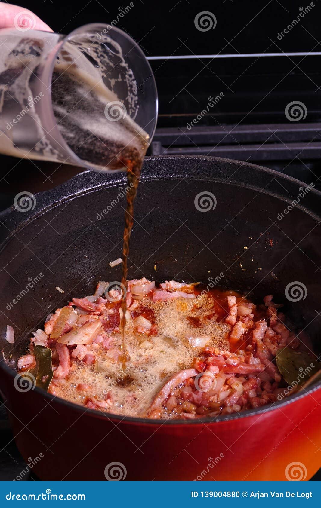 Goulash or beef stew cooking. Beer is being added