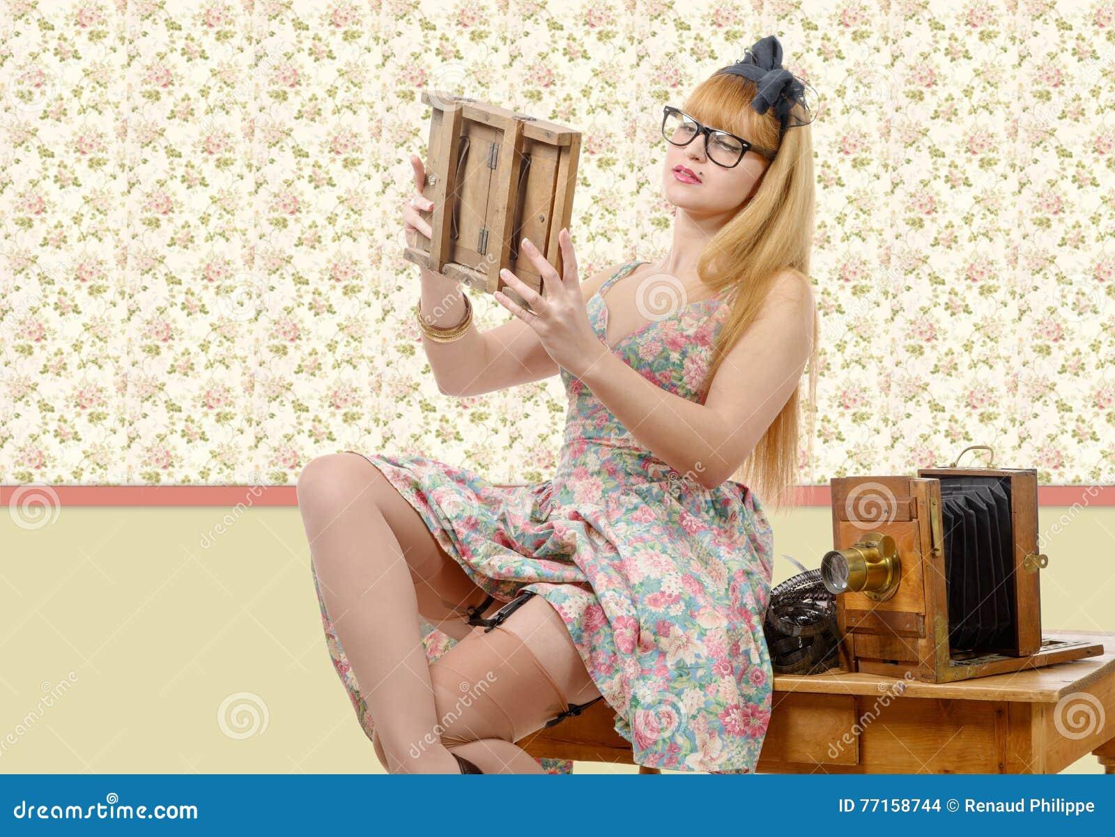 Goupille sexy vers le haut de fille avec le vieil appareil-photo en bois de photo