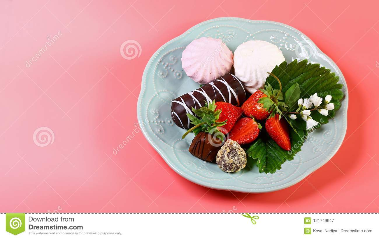 Gourmet Chocolate Covered Strawberries for Valentine`s Day, on a plate isolated on a pink background. Copy space
