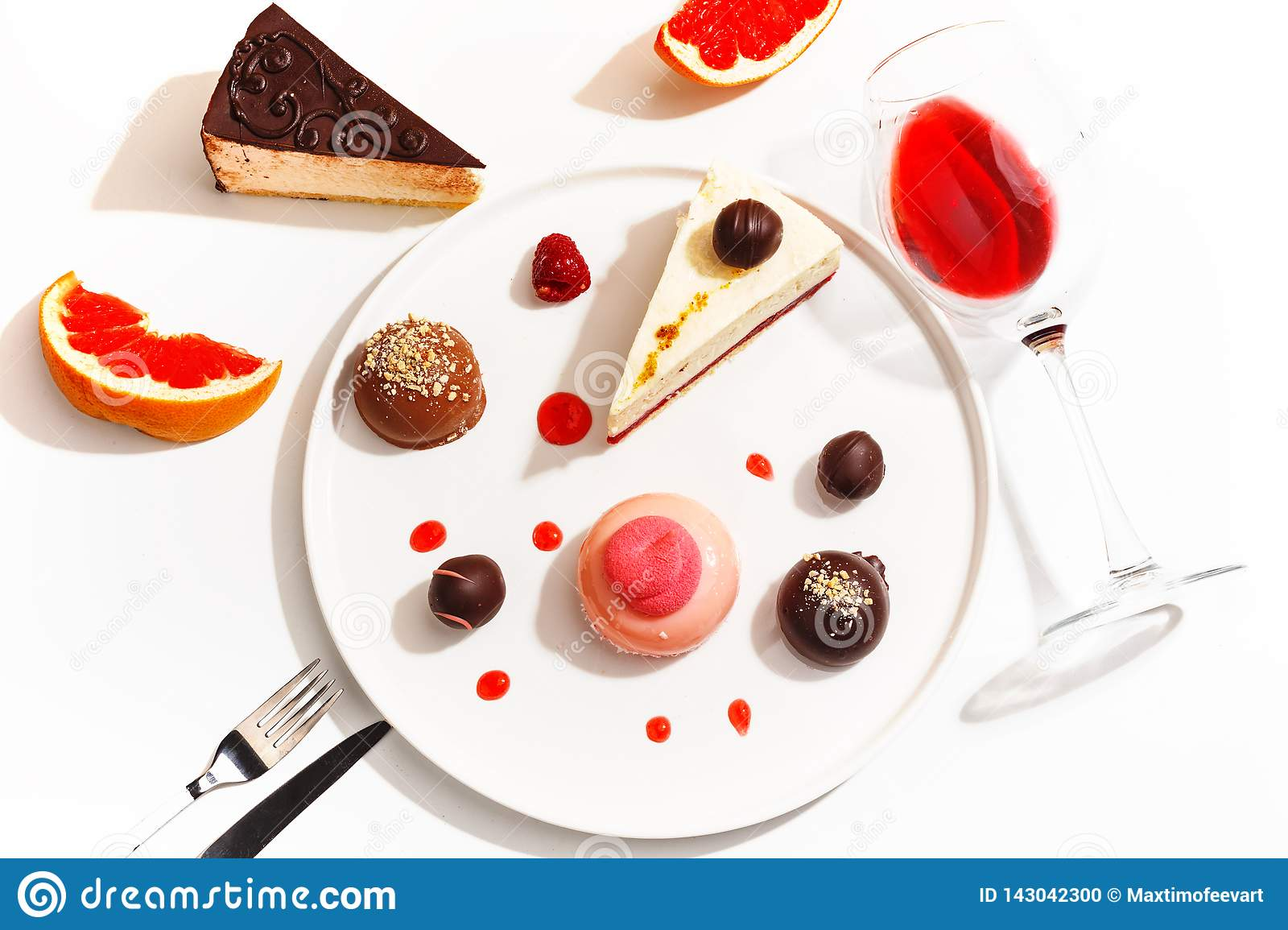 Gourmet desserts and grapefruit slices on a white plate. Top view