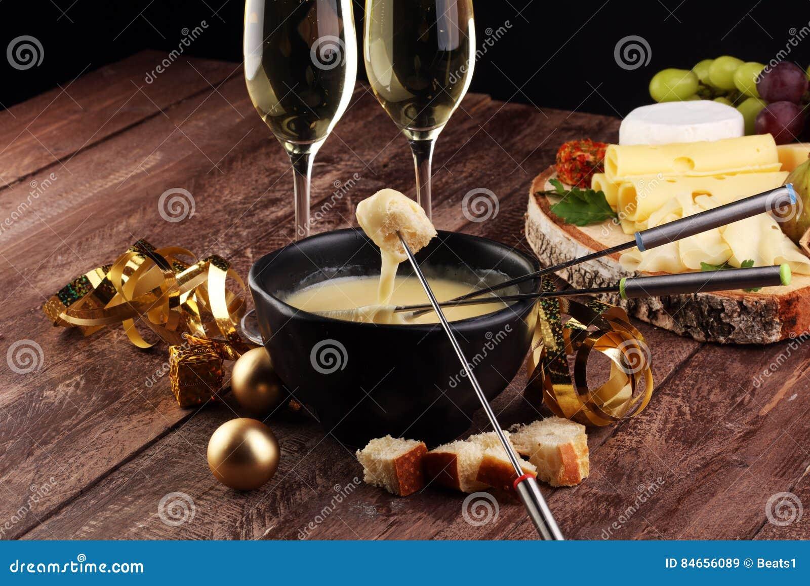 Gourmet- schweizisk fonduematställe på en vinterafton med blandade ostar på ett bräde tillsammans med en upphettad kruka av ostfo