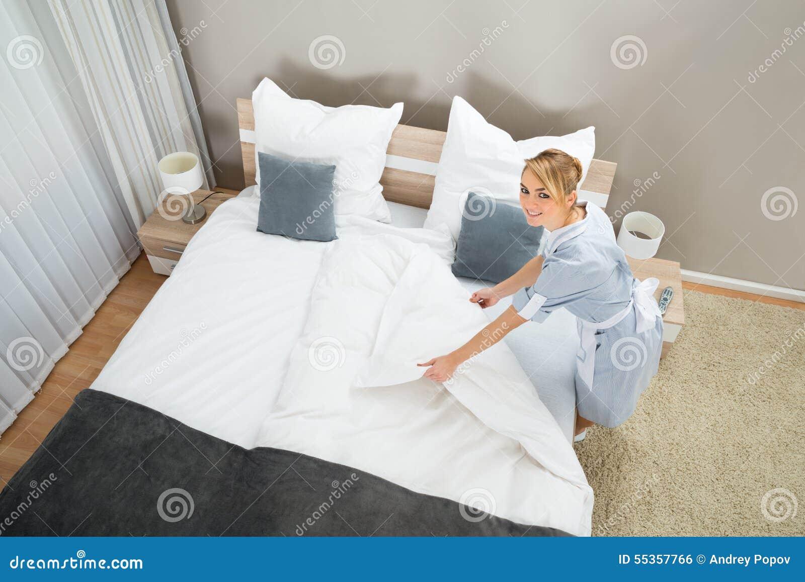 Governante femminile che fa letto con i vestiti del letto