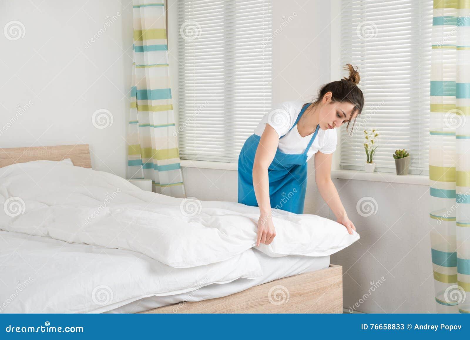 Governante femminile che sistema lenzuolo sul letto