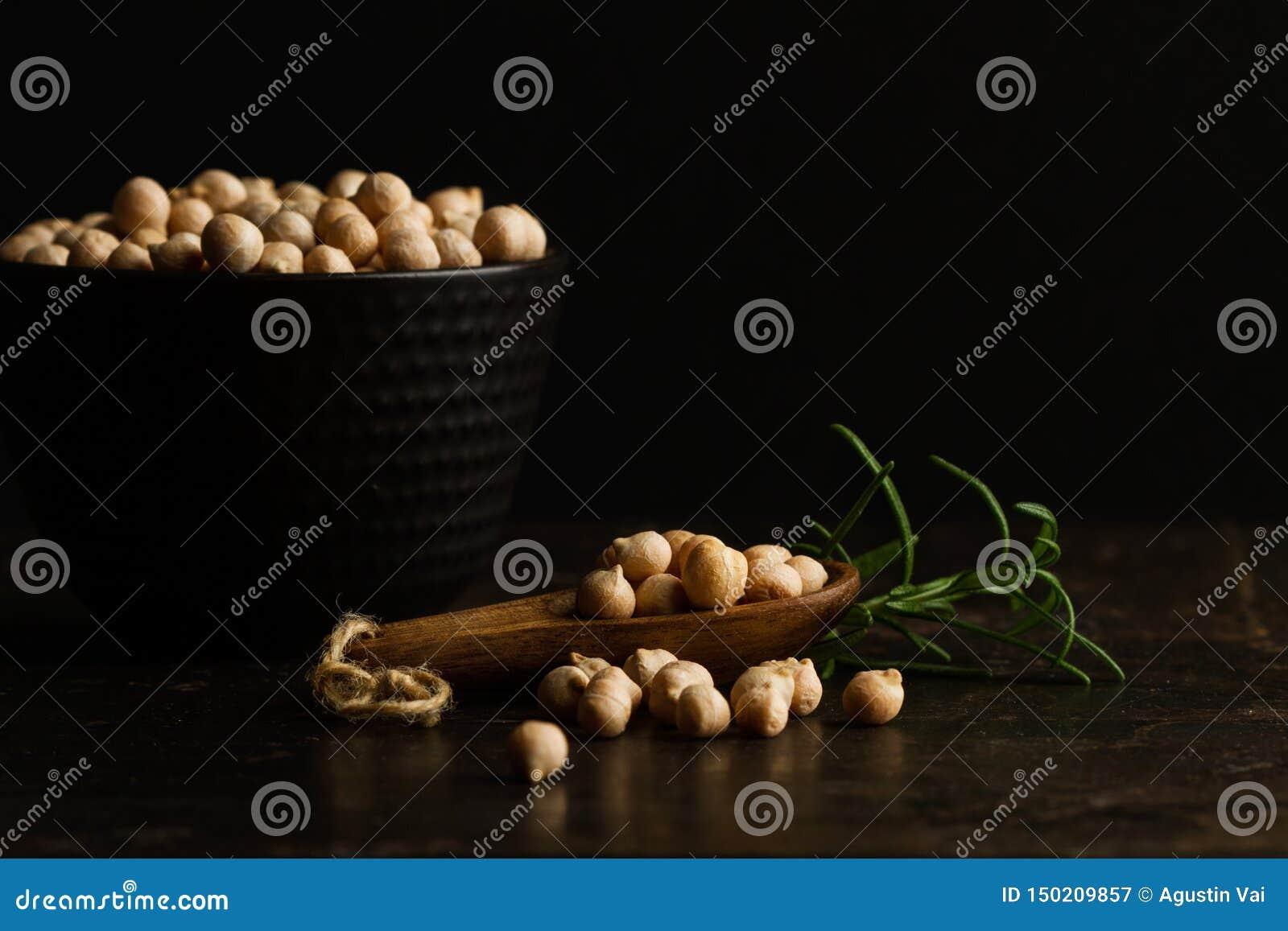 Grãos-de-bico em um bowland cerâmico preto em uma colher de madeira