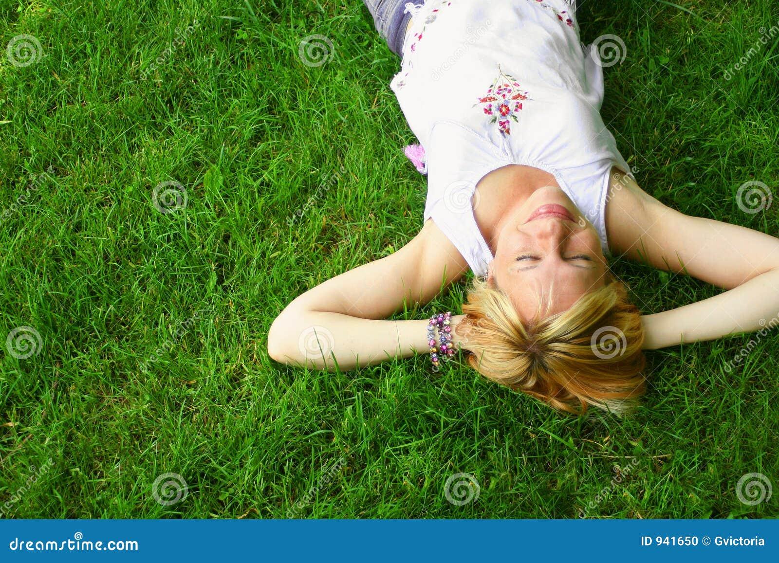 Gräs som lägger den avslappnande kvinnan
