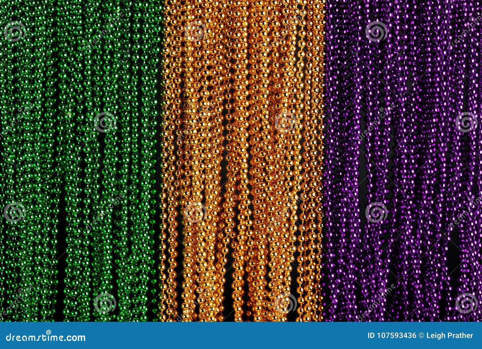 Gräsplan, guld och purpurfärgade Mardi Gras pärlor