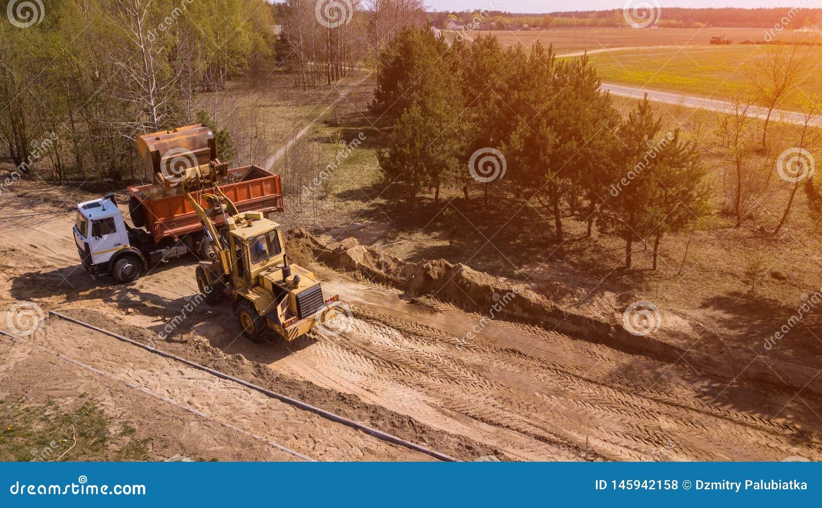 Grävskopan laddar sanden in i lastbilen Arbetare gör vägen