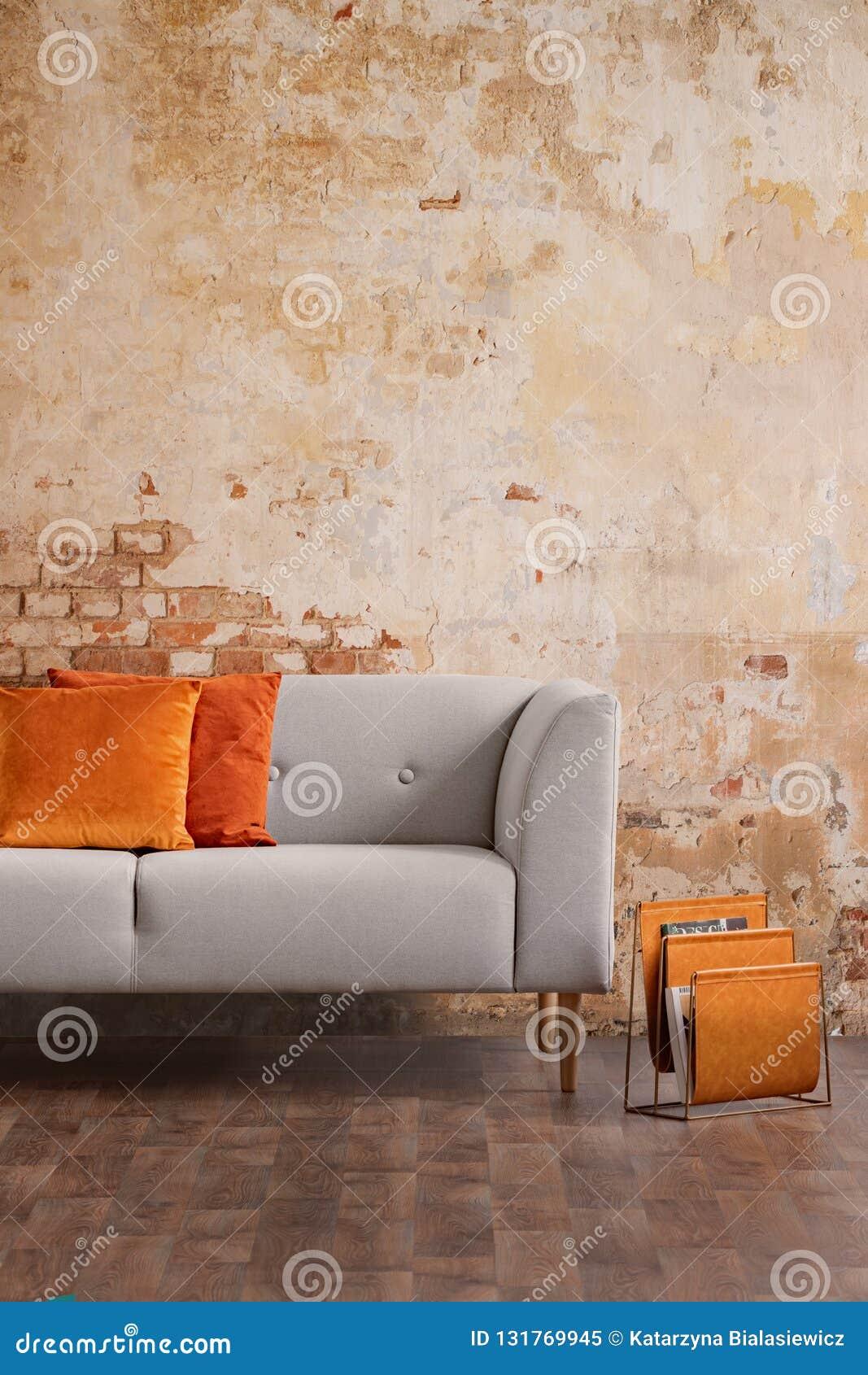 Grå färgsoffa mot väggen för röd tegelsten i modern vardagsruminre Verkligt foto